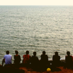 Trekkers sitting by a cliff at Gokarna